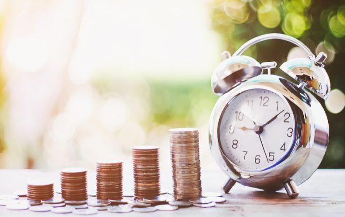 four piles of coins next to an alarm clock